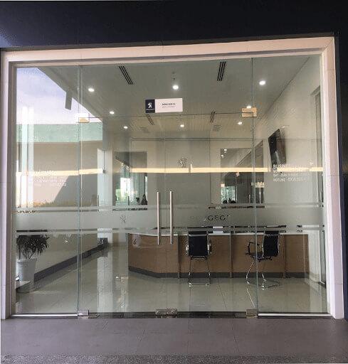 Cửa kính bản lề sàn với các chi tiết kính, phụ kiện và khung cố định kính.