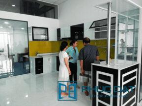 Khách hàng tham quan tủ bếp sử dụng sơn kính cao cấp của Phúc Đạt.