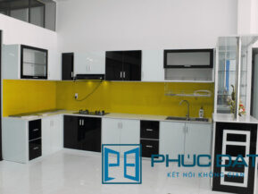 Mẫu tủ bếp trưng bày tại showroom Phúc Đạt ốp kính bếp màu trắng sữa, vàng và đen.